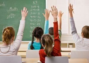 Students in classroom raising their hands to answer their teacher's question. Horizontal shot.