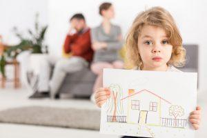 Upset little boy holding a drawing of a house, with his parents sitting angry on a couch in the blurry background