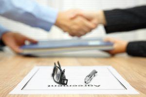 businessman and businesswoman are shaking hands and exchanging folder  after agreement was reached